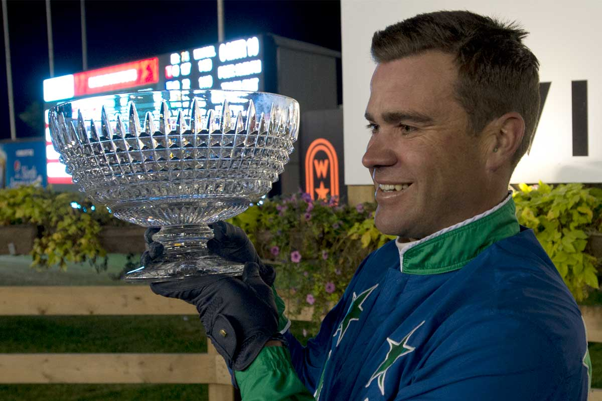 Mohawk Million winner holding the trophy with Woodbine logo in the background