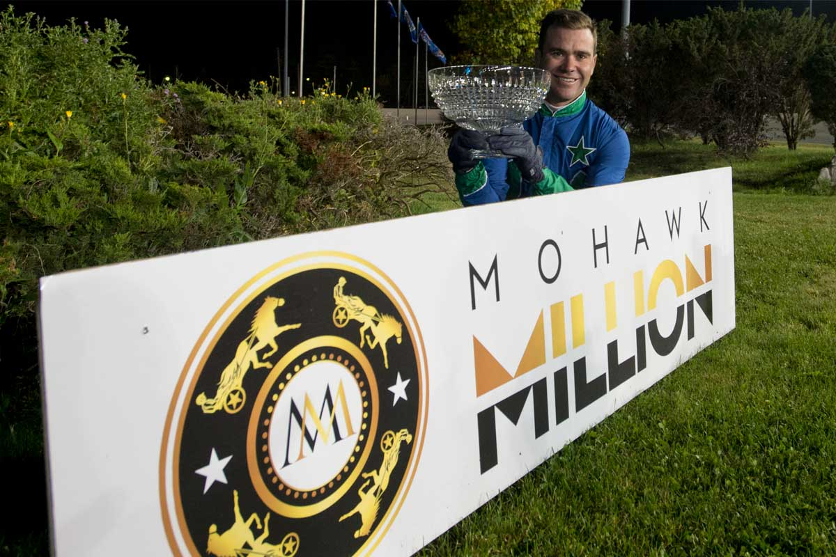 Mohawk Million winner holding the trophy while sitting behind the Mohawk Million logo and brand name card