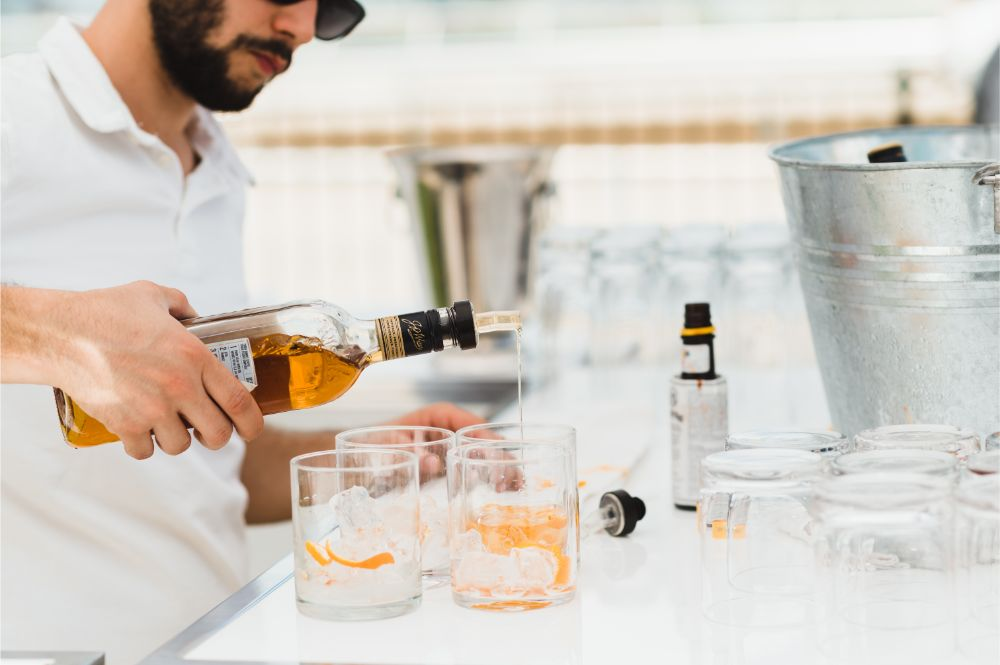 A man pours a drink at White Party