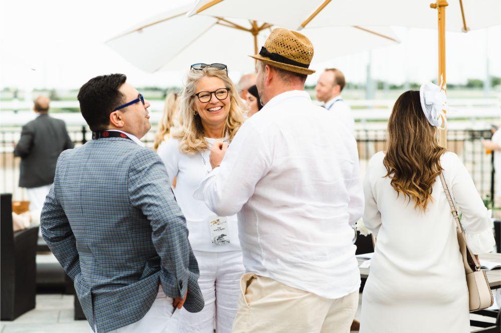 Three guests share a joke at White Party