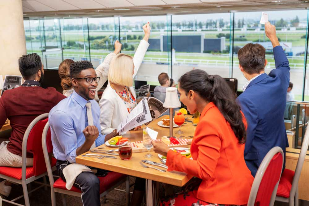 Post parade dining packages. Guests cheering the horses from Post Parade Dining Room at Woodbine Racetrack