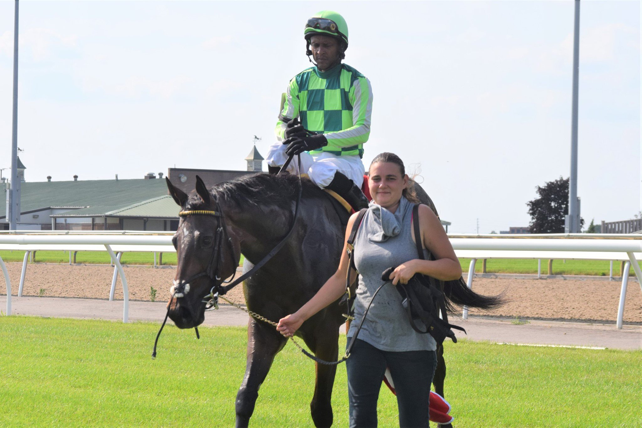 Crystal Todd with a jockey on a horse on a racetrack.