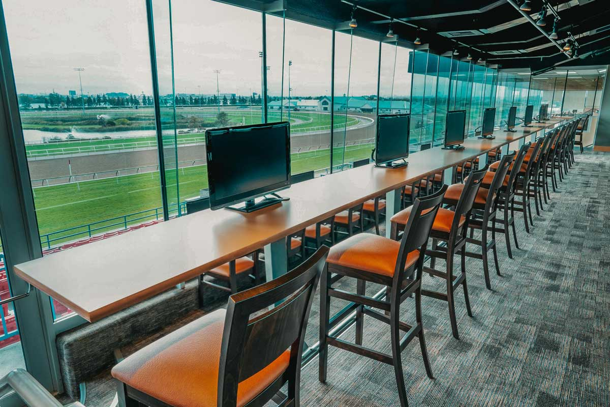 Finish Line O&T Lounge for Owners and Trainers trackside view with chairs and screens