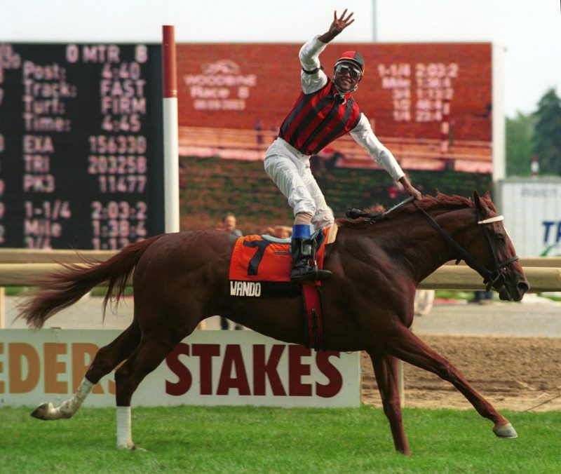 Jockey Patrick Husbands guides Wando to victory in the 2003 Queen's Plate. The Canadian Triple Crown winner was trained by Mike Keogh. Keogh is a 2020 Canadian Horse Racing Hall of Fame Inductee.