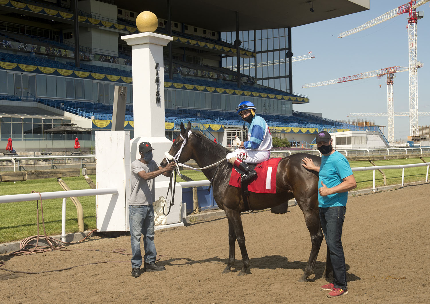 Trainer Darwin Banach (right) in the winner's circle celebrating a special victory by Samurai Queen on June 19 at Woodbine Racetrack. (Michael Burns Photo)